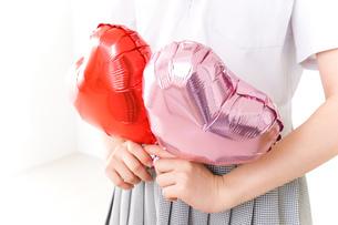 ハートマークを持つ若い女性の写真素材 [FYI04717817]
