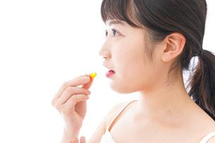 薬・サプリメントを飲む若い女性の写真素材 [FYI04718101]