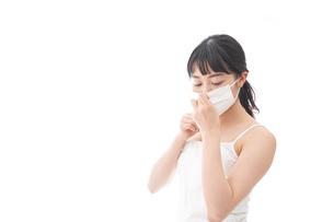 花粉症・風邪・インフルエンザに苦しみマスクをする若い女性の写真素材 [FYI04718127]