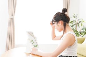 スキンケア・メイクをする若い女性の写真素材 [FYI04718423]