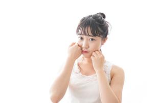スキンケア・メイクをする若い女性の写真素材 [FYI04718434]