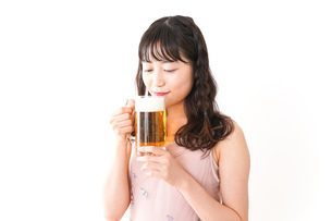 グラスを持ちビールを飲む若い女性の写真素材 [FYI04718442]