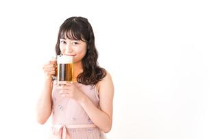 グラスを持ちビールを飲む若い女性の写真素材 [FYI04718460]