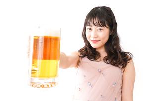 グラスを持ちビールを飲む若い女性の写真素材 [FYI04718461]