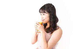 グラスを持ちビールを飲む若い女性の写真素材 [FYI04718464]