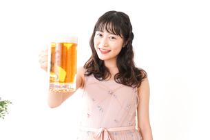 グラスを持ちビールを飲む若い女性の写真素材 [FYI04718471]