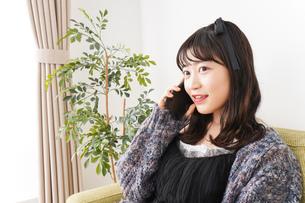 家でスマートフォンを使う若い女性の写真素材 [FYI04718834]