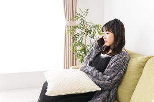家でスマートフォンを使う若い女性の写真素材 [FYI04718836]