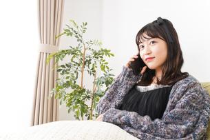 家でスマートフォンを使う若い女性の写真素材 [FYI04718837]