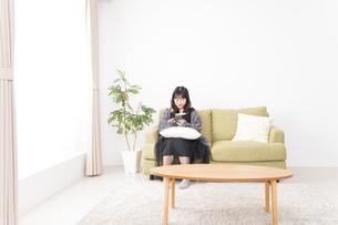 家でスマートフォンを使う若い女性の写真素材 [FYI04718842]