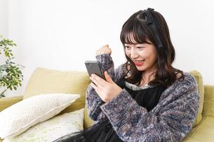 家でスマートフォンを使う若い女性の写真素材 [FYI04718849]