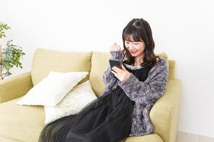 家でスマートフォンを使う若い女性の写真素材 [FYI04718851]