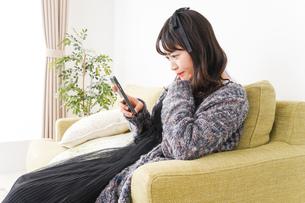 家でスマートフォンを使う若い女性の写真素材 [FYI04718863]