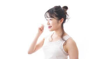 歯磨きをする若い女性の写真素材 [FYI04718888]