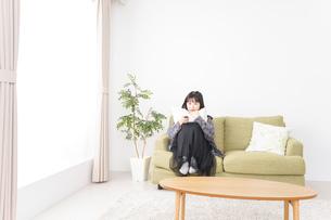 家でテレビを見る若い女性の写真素材 [FYI04718989]