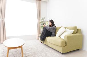 家でテレビを見る若い女性の写真素材 [FYI04718992]