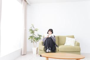 家でテレビを見る若い女性の写真素材 [FYI04718993]