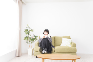 家でテレビを見る若い女性の写真素材 [FYI04718994]