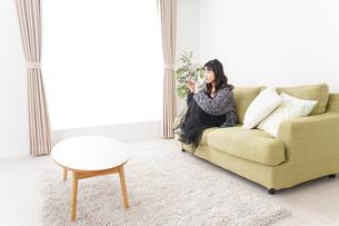 家でテレビを見る若い女性の写真素材 [FYI04718995]