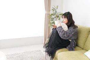 家でテレビを見る若い女性の写真素材 [FYI04718997]