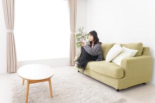 家でテレビを見る若い女性の写真素材 [FYI04718998]