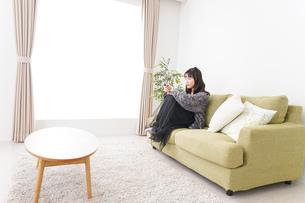 家でテレビを見る若い女性の写真素材 [FYI04718999]