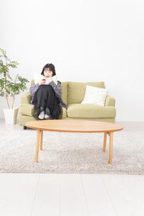 家でテレビを見る若い女性の写真素材 [FYI04719006]