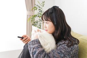 家でテレビを見る若い女性の写真素材 [FYI04719007]