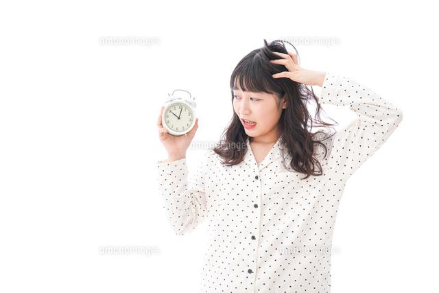寝坊をする若い女性の写真素材 [FYI04719110]