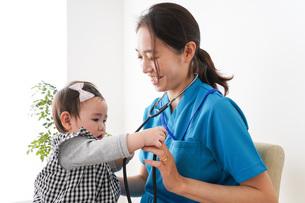 赤ちゃんの診察をする若いドクターの写真素材 [FYI04719491]