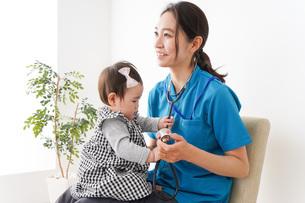 赤ちゃんの診察をする若いドクターの写真素材 [FYI04719497]