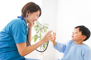 子どもを診察する若い看護師の写真素材 [FYI04719498]