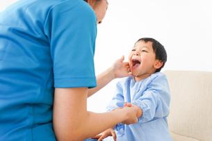 子どもを診察する若い看護師の写真素材 [FYI04719515]