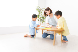 幼稚園で折り紙をする子どもと先生の写真素材 [FYI04719609]