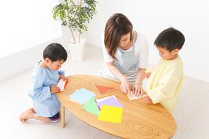 幼稚園で折り紙をする子どもと先生の写真素材 [FYI04719611]