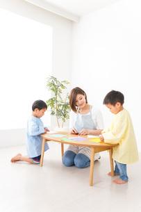 幼稚園で折り紙をする子どもと先生の写真素材 [FYI04719615]