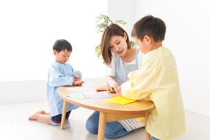 幼稚園で折り紙をする子どもと先生の写真素材 [FYI04719616]