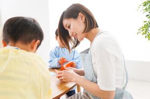 幼稚園で折り紙をする子どもと先生の写真素材 [FYI04719617]