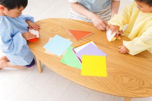 幼稚園で折り紙をする子どもと先生の写真素材 [FYI04719618]