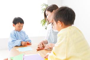 幼稚園で折り紙をする子どもと先生の写真素材 [FYI04719620]
