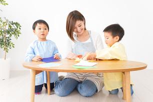 幼稚園で折り紙をする子どもと先生の写真素材 [FYI04719621]