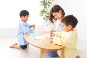 幼稚園で折り紙をする子どもと先生の写真素材 [FYI04719625]