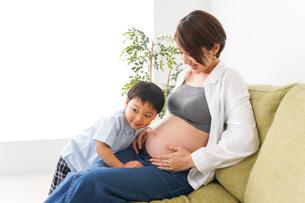 赤ちゃんの鼓動を聞く小さな男の子の写真素材 [FYI04719638]