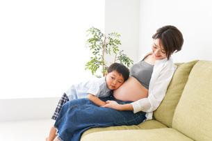 赤ちゃんの鼓動を聞く小さな男の子の写真素材 [FYI04719645]