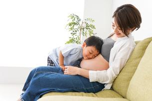 赤ちゃんの鼓動を聞く小さな男の子の写真素材 [FYI04719647]
