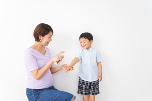 子どもにスプレーをするお母さんの写真素材 [FYI04719795]