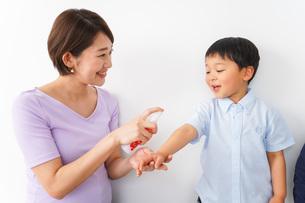 子どもにスプレーをするお母さんの写真素材 [FYI04719796]