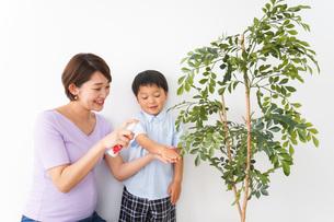 子どもにスプレーをするお母さんの写真素材 [FYI04719814]