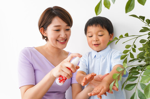 子どもにスプレーをするお母さんの写真素材 [FYI04719816]