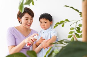 子どもにスプレーをするお母さんの写真素材 [FYI04719818]